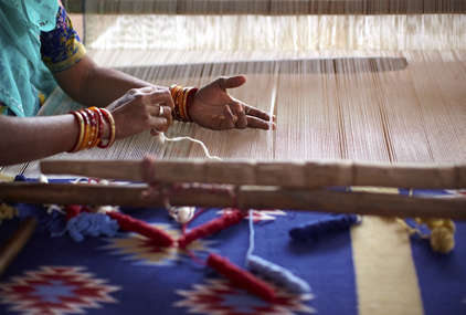 Woman hand weaving a carpet with a manual loom in India